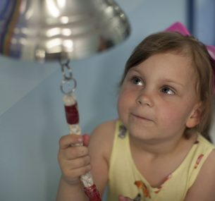 Olivia rings the end of treatment bell