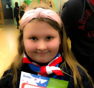 Girl in girl guides outfit with scarf and certificate