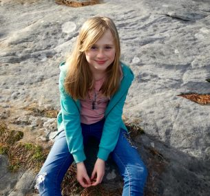 Beth girl sitting on rocks