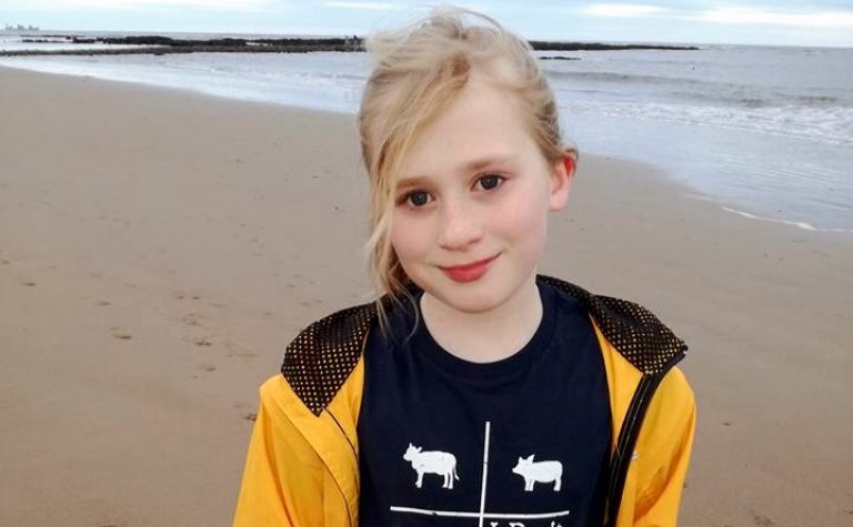 girl in yellow jacket by the beach