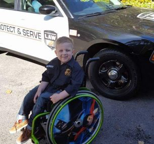 Child in a wheelchair next to a police car