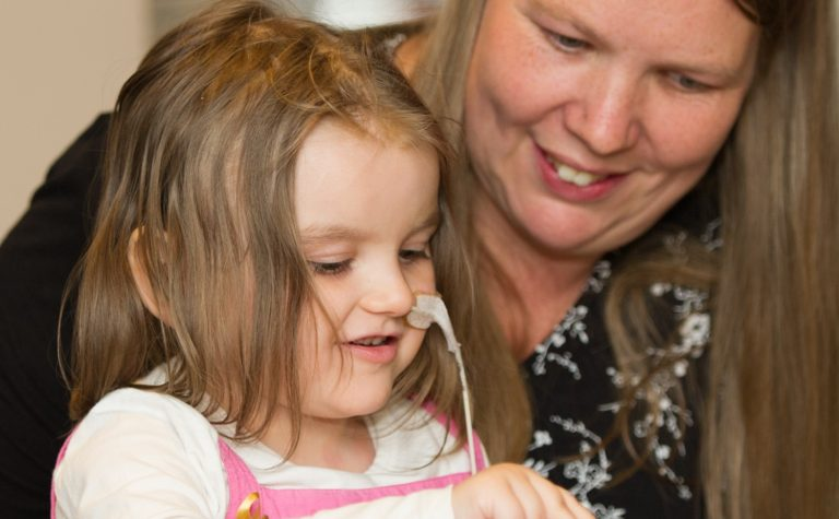 Lucy who was diagnosed with a brain tumour sitting on her mother's lap