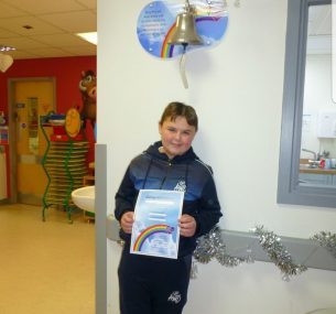 boy holding certificate standing underneath end of treatment bell