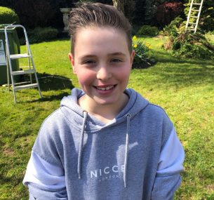 Boy in grey hoodie in garden