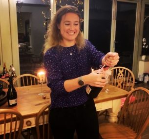 Maisie W celebrating with bottle of bubbly becoming a qualified Doctor