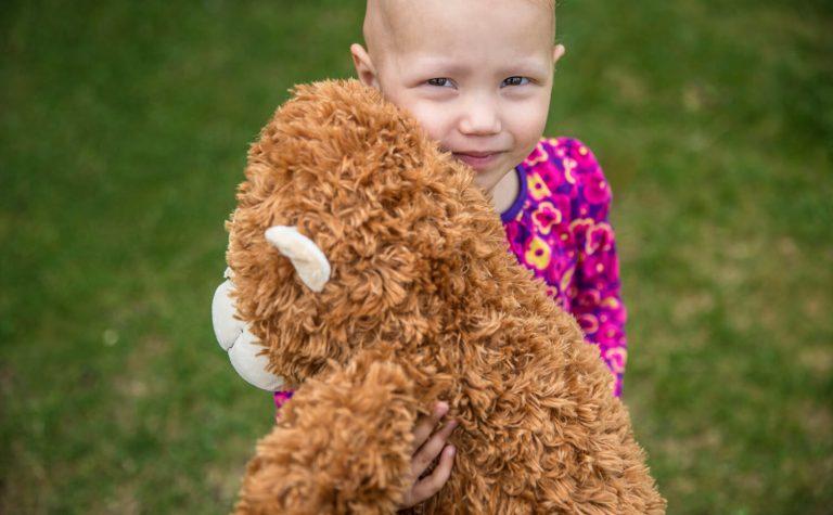 Eva hugging her teddy bear