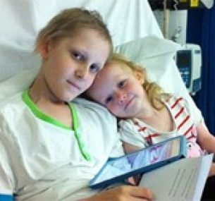 Jarvis in bed during treatment, joined by his younger sister.