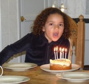 Jemma blows out candles on a cake.