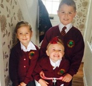 Lewis smiles, standing with his siblings.