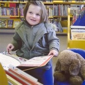 Louisa opens a book in a library.
