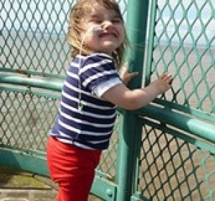 Lucy smiles, holding onto a metal fence.