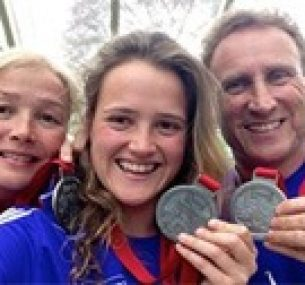 Maisie celebrates with her mother and father after completing a marathon.