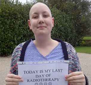 "Millie holds a sign reading ""Today is my last day of radiotherapy""."