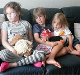 Olivia sits on sofa accompanied by her siblings.