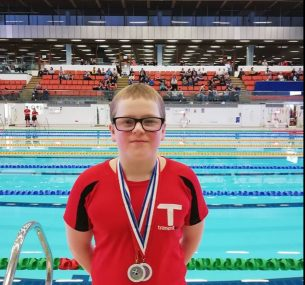 Boy in red top with medals in front of swimming pool