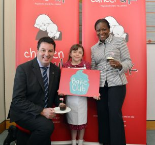 Two adults and a young girl with cup cakes
