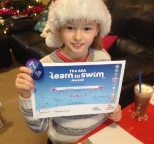 Bethan in santa hat holding swimming certificate