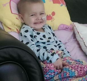 A small child smiling on a sofa