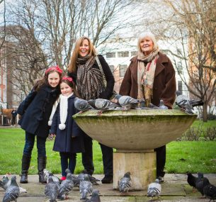 A family stands with a group of pigeons