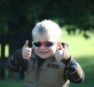 A small boy gives double thumbs up