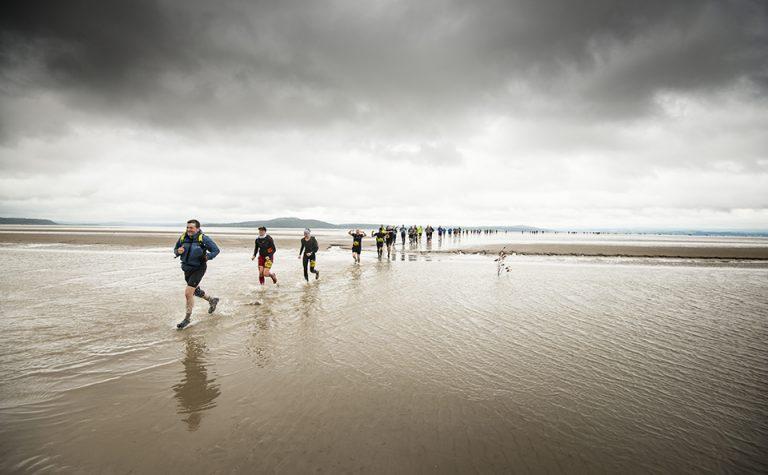 Participants trekking across wet sand