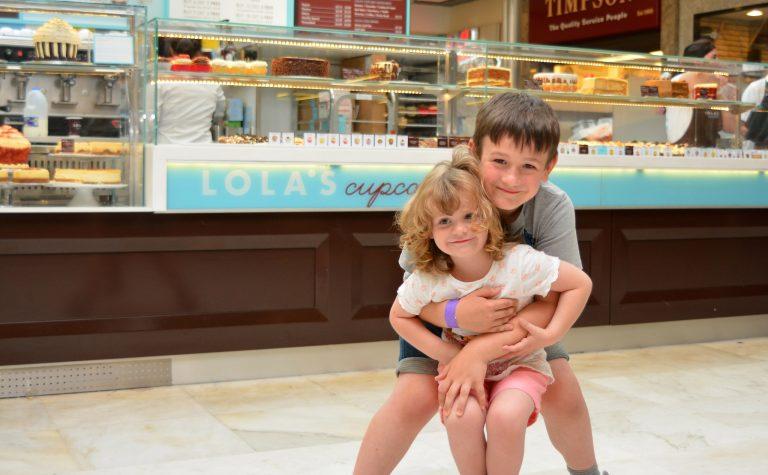Two children outside a cupcake shop