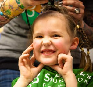A small girl having her hair styled