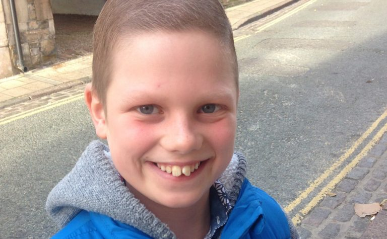 boy in blue gilet smiling