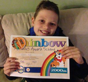 boy Isaac holding swimming award