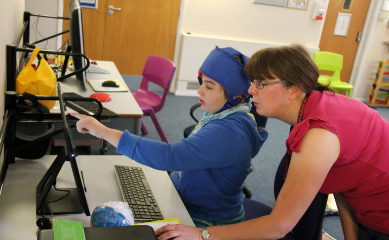 an adult and a child using a computer