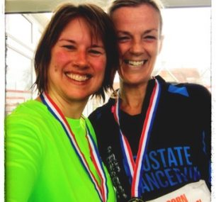 Two ladies posing after running a half marathon