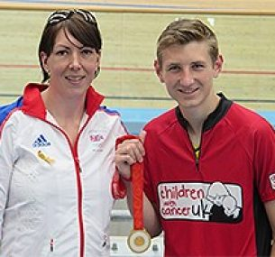 Two people at a velodrome with a medal