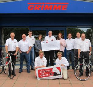 The Grimme cycling team with a cheque