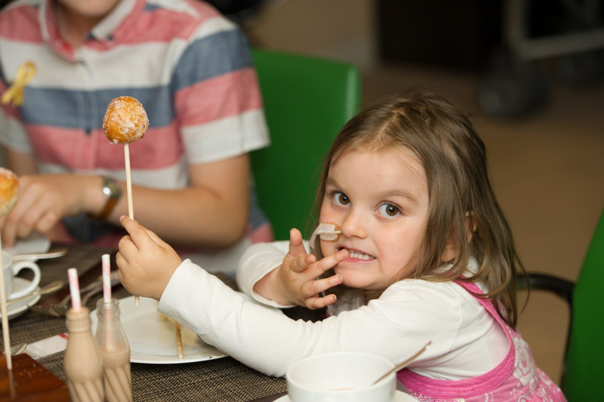 Young girl holding a cake on a stick