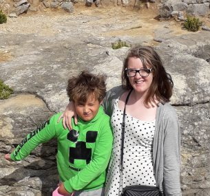 Mother and son standing by rocks
