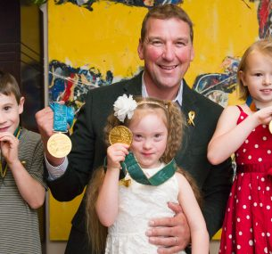 Matthew Pinsent posing with children and gold medals