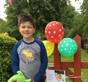 Boy standing next to gate with balloons