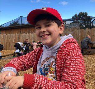 Josh smiling wearing red hat smiling