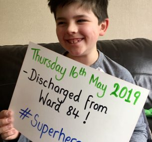 boy holding discharge sign