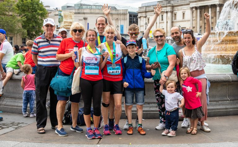 group of people at fountain with running vest and medals ASICS britsh 10k (1)
