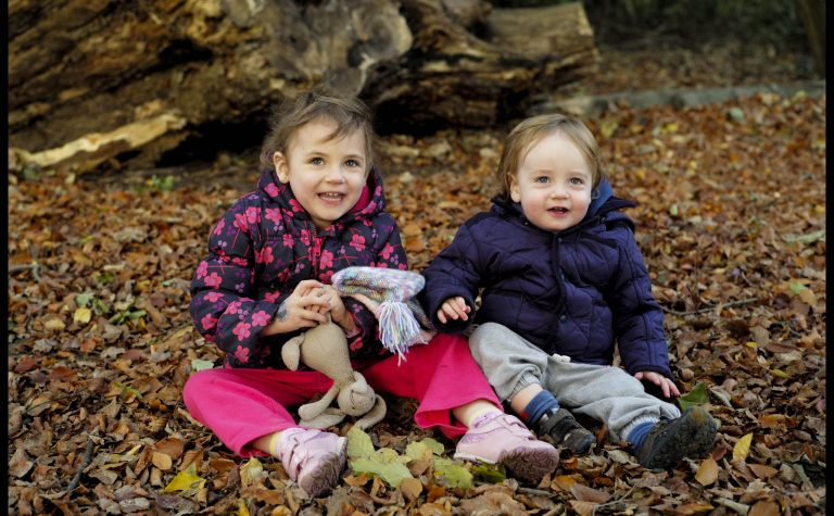 Two children sitting in the autumn leaves.