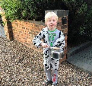 Boy in dressing gown holding pot and wooden spoon