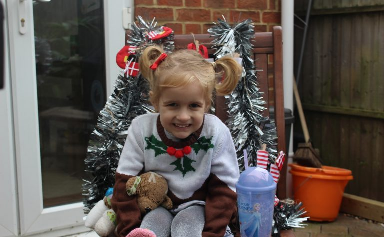 Blonde girl in Christmas jumper sitting on chair