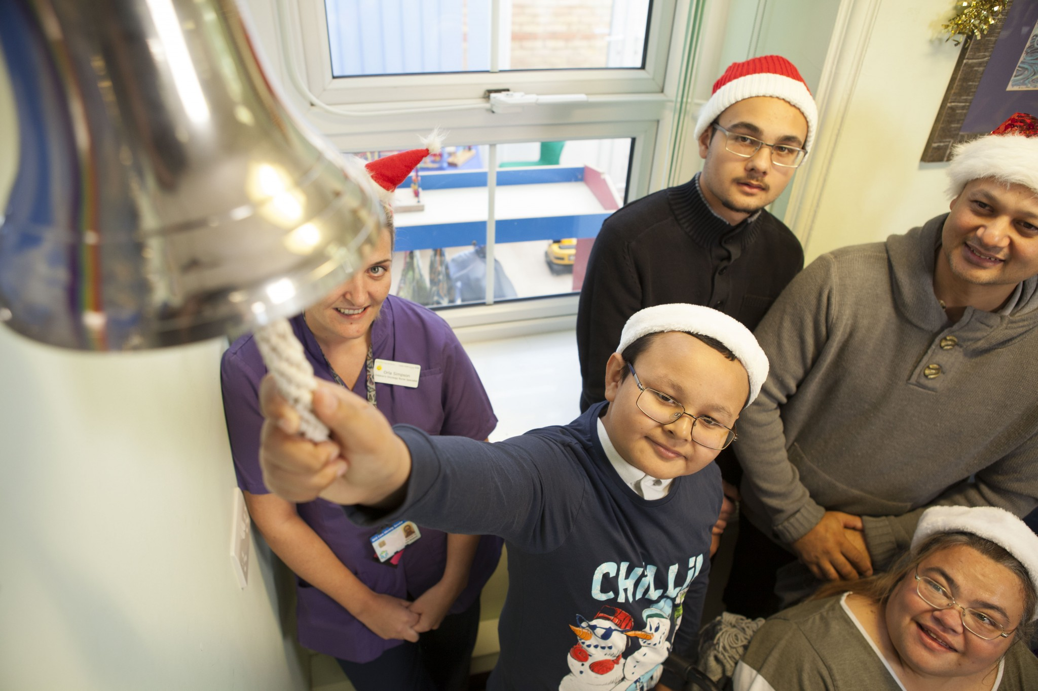 dylan ringing the bell with santa hat