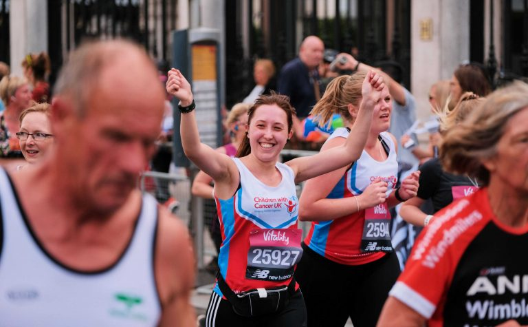 Woman running with arms up in Oxford Half Marathon