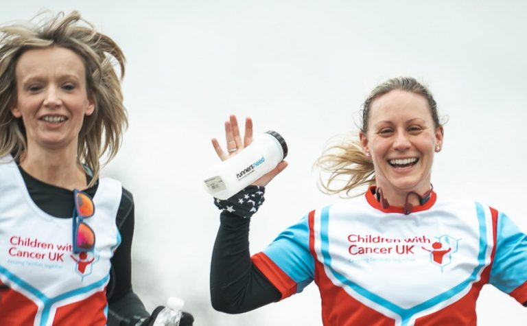 two female runners wearing charity vests smiling and waving. 1920x800