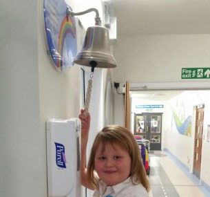Girl ringing the end of treatment bell