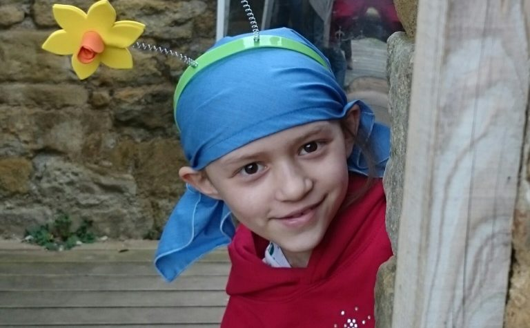 A little girl wearing a scarf with daffodils on her head