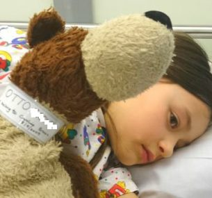A little girl lying in a hospital bed