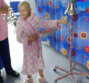 A little girl ringing the end of treatment bell